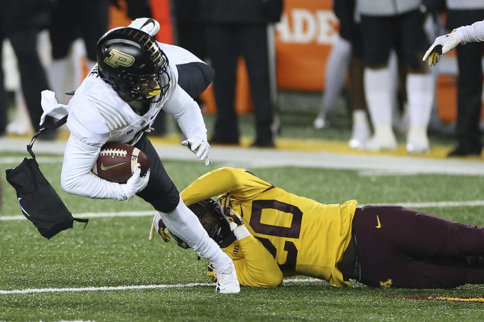 Purdue wide receiver Rondale Moore (4) is tackled by Minnesota linebacker Donald Willis (20) during the second half of an NCAA college football game Friday, Nov. 20, 2020, in Minneapolis. Minnesota won 34-31. (AP Photo/Stacy Bengs)