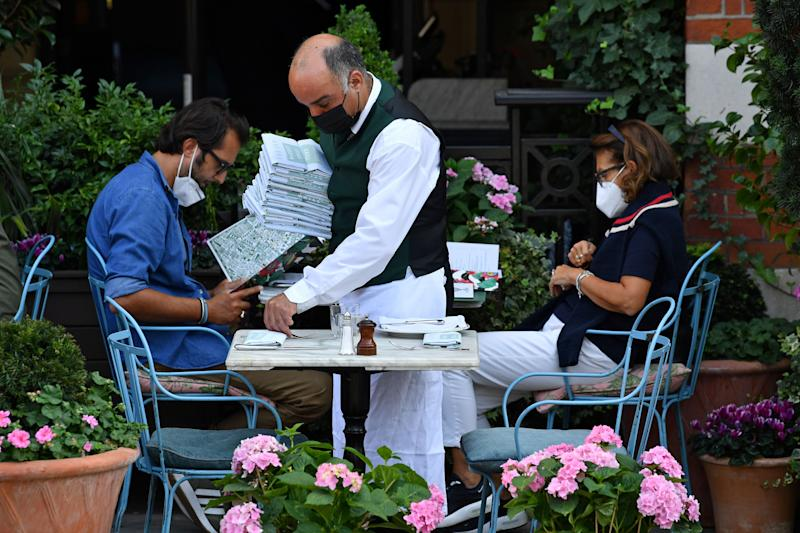 A waiter wearing a face mask or covering due to the COVID-19 pandemic, lays a table outside a restaurant in Covent Garden, London on September 22, 2020. - The British government announced fresh steps Tuesday to try and stop a coronavirus surge in England, as the World Health Organization warned that new cases worldwide soared to almost two million last week in a grim new record. The measure included early closing time for pubs and restaurants, a resumption of advice for people to work from home, coupled with new penalties for breaking the rules. (Photo by Ben STANSALL / AFP) (Photo by BEN STANSALL/AFP via Getty Images)
