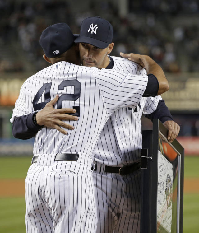New York Yankees starting pitcher Andy Pettitte, who pitched his final game at Yankee Stadium on Sunday, embraces relief pitcher Mariano Rivera, who is retiring at the end of the season, after Rivera and Derek Jeter presented Pettitte with a base from Sunjday's game, Wednesday, Sept. 25, 2013, in New York. (AP Photo/Kathy Willens)
