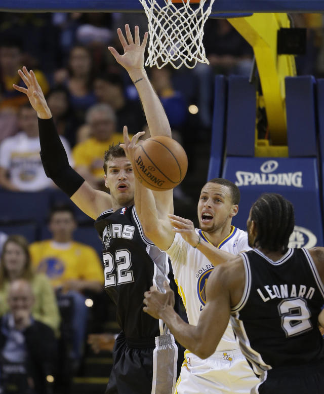 Golden State Warriors guard Stephen Curry loses control of the ball as San Antonio Spurs center Tiago Splitter (22) and forward Kawhi Leonard (2) defend during the first quarter of an NBA basketball game Saturday, March 22, 2014, in Oakland, Calif. (AP Photo/Eric Risberg)