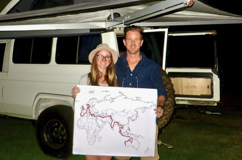 Jolie King and Mark Firkin hold a map showing their journey in front of their Landcruiser.