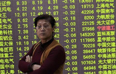 An investor stands in front of an electronic board showing stock information filled with green figures indicating falling prices at a brokerage house in Hangzhou