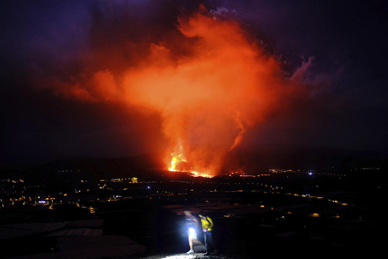Two people walk as lava spews from a volcano on the Canary island of La Palma, Spain in the early hours of Saturday Sept. 25, 2021. A volcano in Spain's Canary Islands is keeping nerves on edge several days since it erupted, producing loud explosions, a huge ash cloud and cracking open a new fissure that spewed out more fiery molten rock. The prompt evacuations are credited with helping avoid casualties but scientists say the lava flows could last for weeks or months. (AP Photo/Daniel Roca)
