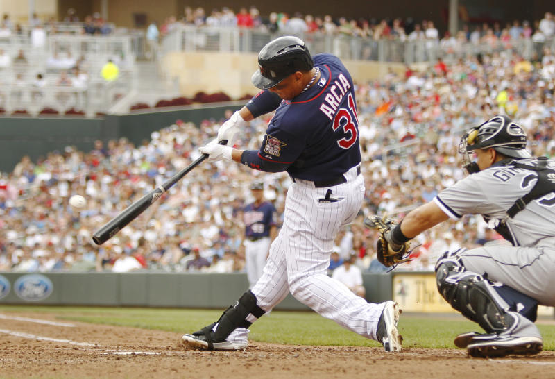 Minnesota Twins' Oswaldo Arcia (31) hits an RBI single against Chicago White Sox starting pitcher John Danks as Hector Gimenez, right, catches during the fifth inning of a baseball game, Thursday, June 20, 2013, in Minneapolis. (AP Photo/Genevieve Ross)