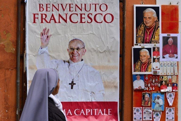 "A nun walks past a board showing a picture of Pope Francis (L) and pictures of Pope Emeritus Benedict on March 15, 2013 at the Vatican. Pope Francis flew in to a papal residence near Rome on Saturday for an unprecedented encounter with ""pope emeritus"" Benedict XVI -- the first time a pontiff has met his predecessor"