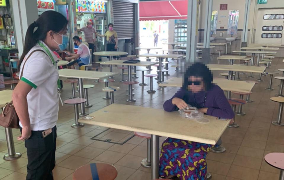 A woman sat on a marked seat at a food centre in Aljunied Avenue 2 and refused to leave despite instructions from officers during the enhanced safe distancing period to curb the spread of COVID-19. (PHOTO: Ministry of the Environment and Water Resources)