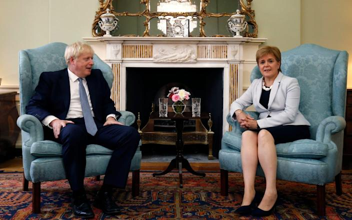 Scotland's First Minister Nicola Sturgeon, right, sits with Britain's Prime Minister Boris Johnson, - Duncan McGlynn/Pool Getty
