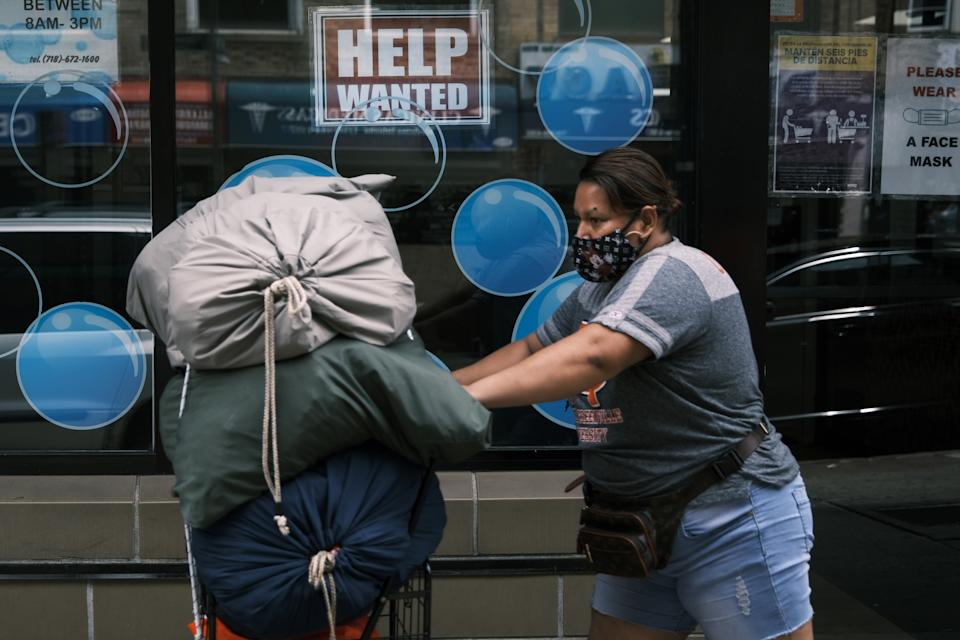 NEW YORK, NEW YORK - JUNE 04: People walk by a Help Wanted sign in the Queens borough of New York City on June 04, 2021 in New York City. The U.S. economy added 559,000 jobs in May, bringing the unemployment rate down to 5.8 percent from 6.1 percent. Despite the positive economic news, millions of Americans are still looking for work or are in need of financial, food, and housing assistance. (Photo by Spencer Platt/Getty Images)