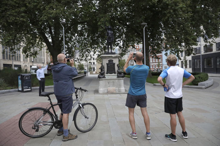 """People look at a new black resin and steel statue entitled """"A Surge of Power (Jen Reid) 2020"""" by artist Marc Quinn after it was put up this morning on the empty plinth of the toppled statue of 17th century slave trader Edward Colston, which was pulled down during a Black Lives Matter protest in Bristol, England, Wednesday, July 15, 2020. On June 7 anti-racism demonstrators pulled the 18-foot (5.5 meter) bronze likeness of Colston down, dragged it to the nearby harbor and dumped it in the River Avon — sparking both delight and dismay in Britain and beyond. (AP Photo/Matt Dunham)"""