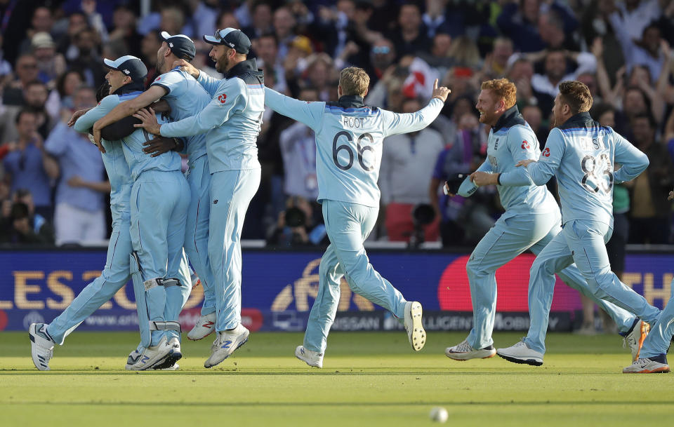 England players mob Jofra Archer after he bowled the super over to win the Cricket World Cup final match between England and New Zealand at Lord's cricket ground in London, Sunday, July 14, 2019. England won after a super over after the scores ended tied after 50 overs each. (AP Photo/Matt Dunham)