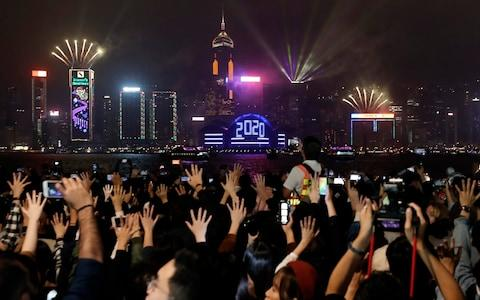<span>Protesters hold up their hands to symbolize the five demands of the pro-democracy movement as New Year's fireworks light up the sky in Hong Kong</span> <span>Credit: AP </span>