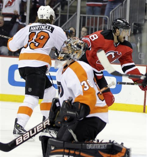 New Jersey Devils' Dainius Zubrus, right rear, elebrates after scoring a goal against Philadelphia Flyers goalie Ilya Bryzgalov, while Flyers' Scott Hartnell skates past during the second period of Game 4 of a second-round NHL hockey Stanley Cup playoff series, Sunday, May 6, 2012, in Newark, N.J. (AP Photo/Julio Cortez)