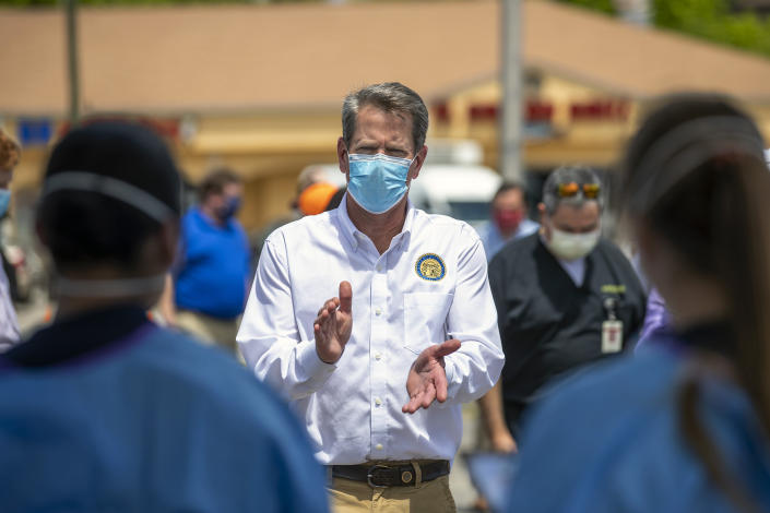 Georgia Gov. Brian Kemp applauds health care workers while touring a community COVID-19 testing site in Gainesville on May 15. (Alyssa Pointer/Atlanta Journal-Constitution via AP)