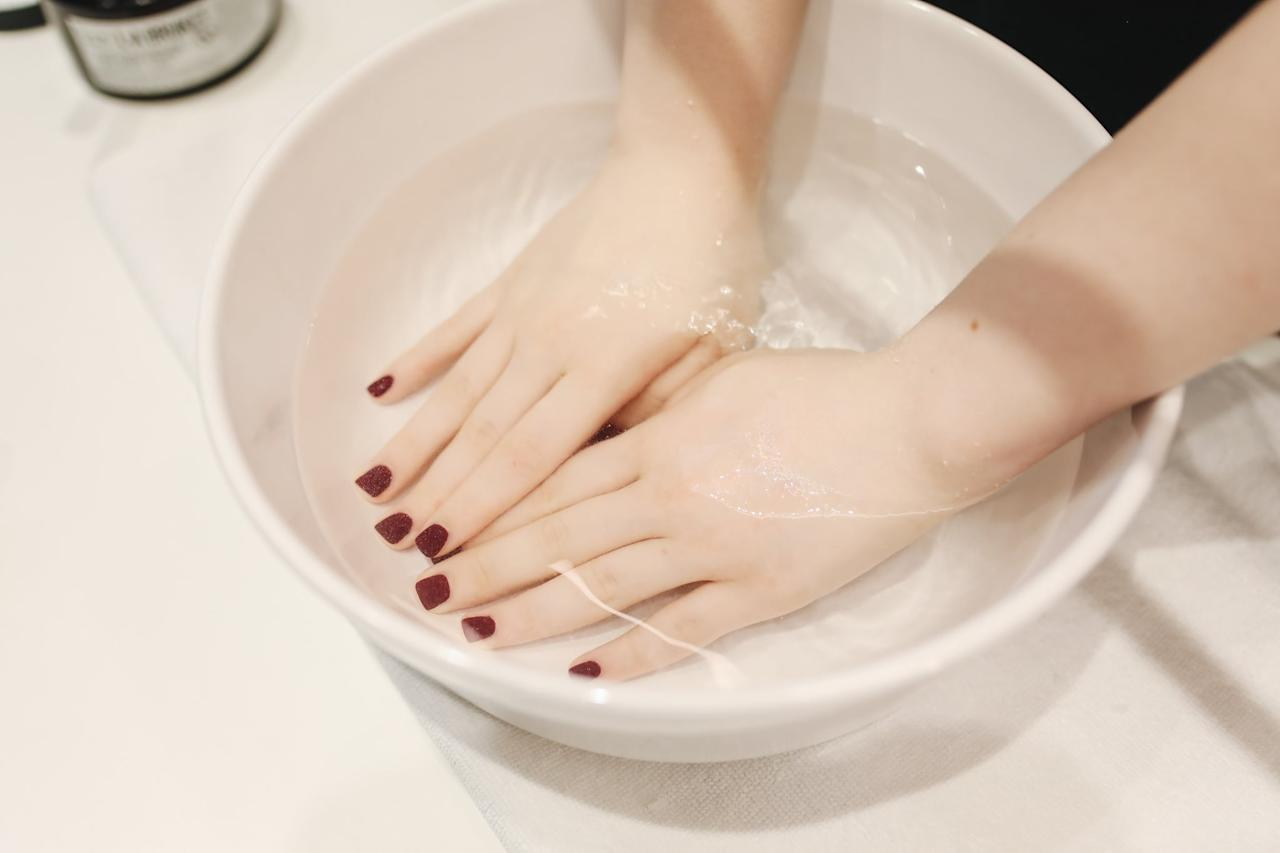 """<p>Soaking your nails off is obviously a little more time intensive, but that doesn't mean it's not still a good method. """"You save plenty of time on the application and long wear of a gel manicure, so the tradeoff is committing to the soak-off process,"""" celebrity nail artist, <a href=""""https://www.instagram.com/enamelle/?hl=en"""" target=""""_blank"""" class=""""ga-track"""" data-ga-category=""""Related"""" data-ga-label=""""https://www.instagram.com/enamelle/?hl=en"""" data-ga-action=""""In-Line Links"""">Elle</a>, told POPSUGAR.</p> <p>You can do this by buffing your nails with a nail file - like this <a href=""""https://www.popsugar.com/buy/Flowery-Duraboard-Nail-File-557910?p_name=Flowery%20Duraboard%20Nail%20File&retailer=ulta.com&pid=557910&price=2&evar1=bella%3Aus&evar9=41910201&evar98=https%3A%2F%2Fwww.popsugar.com%2Fbeauty%2Fphoto-gallery%2F41910201%2Fimage%2F47320114%2FSoak-Em&list1=nail%20polish%2Cnails%2Cbeauty%20tips&prop13=api&pdata=1"""" rel=""""nofollow"""" data-shoppable-link=""""1"""" target=""""_blank"""" class=""""ga-track"""" data-ga-category=""""Related"""" data-ga-label=""""https://www.ulta.com/duraboard-nail-file?productId=VP10582"""" data-ga-action=""""In-Line Links"""">Flowery Duraboard Nail File</a> ($2) - for a minute just to remove the shiny top coat. Then you can fill a bowl with hot water and <a href=""""https://www.popsugar.com/buy/Salon-Gel-Polish-Acetone-Remover-557911?p_name=Salon%20Gel%20Polish%20Acetone%20Remover&retailer=ulta.com&pid=557911&price=5&evar1=bella%3Aus&evar9=41910201&evar98=https%3A%2F%2Fwww.popsugar.com%2Fbeauty%2Fphoto-gallery%2F41910201%2Fimage%2F47320114%2FSoak-Em&list1=nail%20polish%2Cnails%2Cbeauty%20tips&prop13=api&pdata=1"""" rel=""""nofollow"""" data-shoppable-link=""""1"""" target=""""_blank"""" class=""""ga-track"""" data-ga-category=""""Related"""" data-ga-label=""""https://www.ulta.com/salon-gel-polish-acetone-remover?productId=xlsImpprod5100097"""" data-ga-action=""""In-Line Links"""">Salon Gel Polish Acetone Remover</a> ($5) and soak your nails for about 20 minutes, removing the paint with a nail scraper. If it doesn't all come """