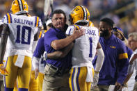 LSU coach Ed Orgeron hugs wide receiver Ja'Marr Chase (1) on the sideline after his touchdown reception in the first half of an NCAA college football game against Texas A&M in Baton Rouge, La., Saturday, Nov. 30, 2019. (AP Photo/Gerald Herbert)
