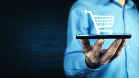 Man holding smartphone with shopping cart icon