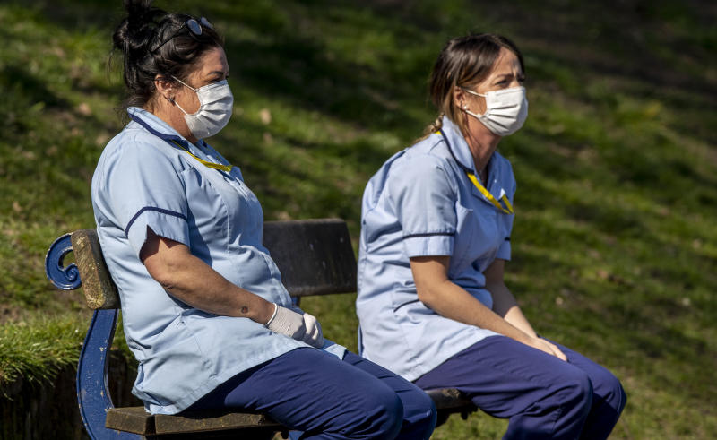 Care workers Carla Martin and Michelle McNicholas take a break from their work and sit on a bench in Sefton Park, Liverpool after Prime Minister Boris Johnson has put the UK in lockdown to help curb the spread of the coronavirus. PA Photo. Picture date: Thursday March 26, 2020. The UK's coronavirus death toll reached 463 on Wednesday. See PA story HEALTH Coronavirus. Photo credit should read: Peter Byrne/PA Wire