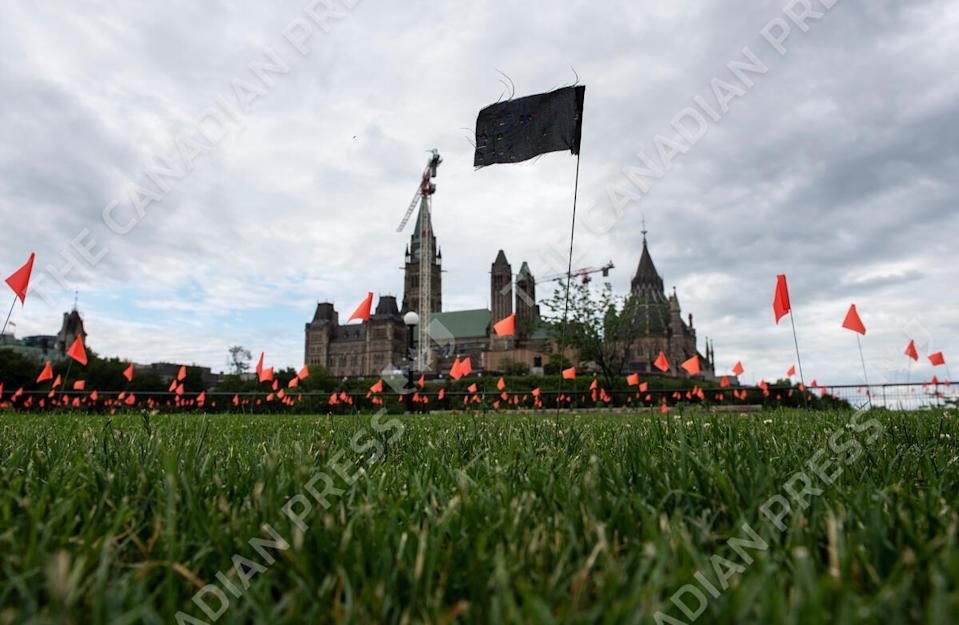 <p>A single black flag flies among orange flags, representing children who died while attending Indian residential schools in Canada, at Major's Hill Park in Ottawa, on Canada Day, Thursday, July 1, 2021. THE CANADIAN PRESS/Justin Tang</p>