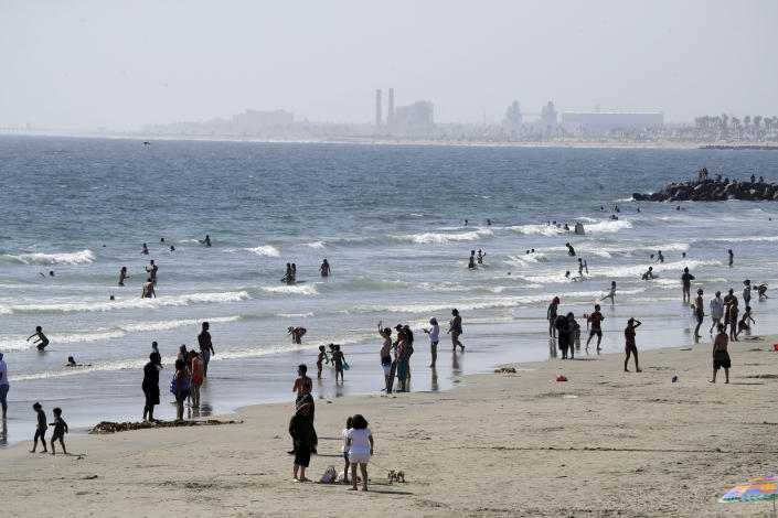 FILE - In this May 24, 2020 file photo, people visit the beach in Newport Beach, Calif., during the coronavirus pandemic. Beachgoers are being urged to practice social distancing to guard against COVID-19. (AP Photo/Marcio Jose Sanchez, File)