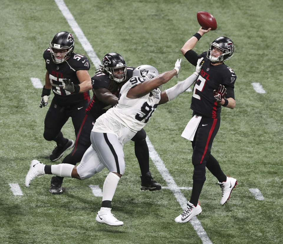 Atlanta Falcons quarterback Matt Ryan throws a touchdown pass to wide receiver Calvin Ridley under pressure from Las Vegas Raiders defensive tackle Johnathan Hankins during the second quarter of an NFL football game on Sunday, Nov 29, 2020, in Atlanta. (Curtis Compton/Atlanta Journal-Constitution via AP)