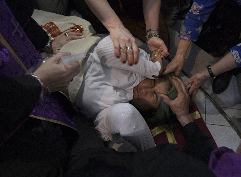 Bishop Manuel Acuna sprinkles holy water on a woman during a ritual at the 'El Buen Pastor' parish in Santos Lugares, on the outskirts of Buenos Aires (AFP Photo/Juan Mabromata)