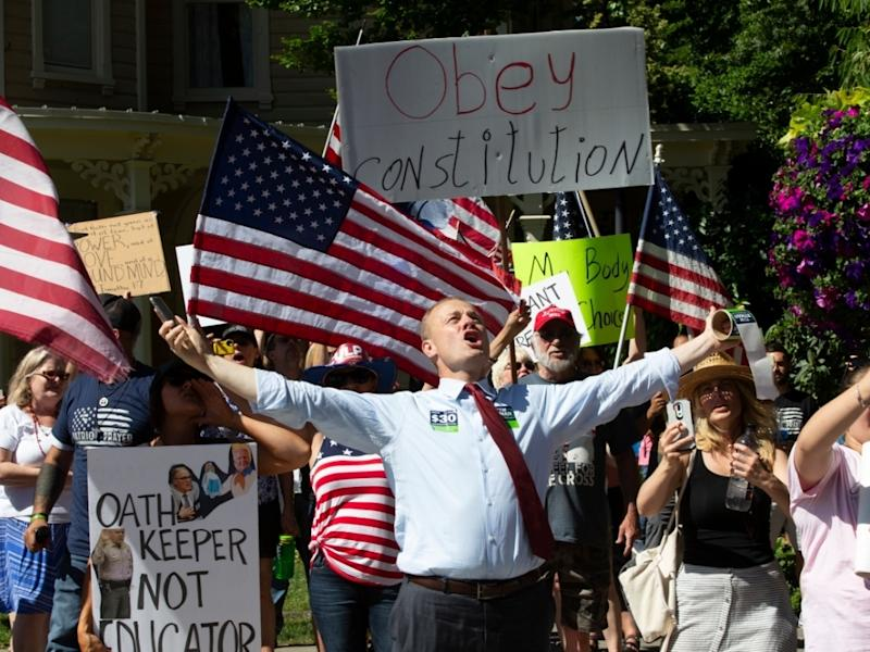 Washington state gubernational candidate and anti-tax activist Tim Eyman (center) joins members of Patriot Prayer and Peoples Rights Washington in a rally against Washington's mask mandate across the street from Vancouver City Hall on June 26, 2020.
