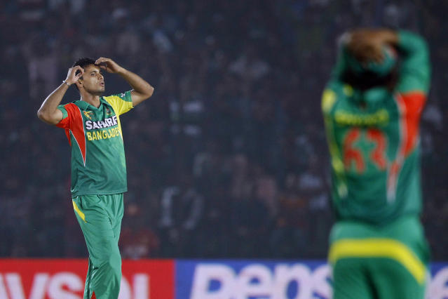 Bangladesh's Mashrafe Mortaza, left, reacts after delivering a ball during the Asia Cup one-day international cricket tournament against India in Fatullah, near Dhaka, Bangladesh, Wednesday, Feb. 26, 2014. (AP Photo/A.M. Ahad)