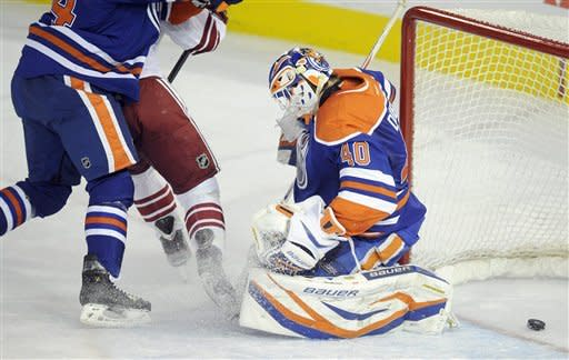 Edmonton Oilers' Corey Potter attempts to stop Phoenix Coyotes' Ray Whitney, center, as he scores on Oilers goalie Devan Dubnyk during the during the first period of an NHL hockey game, Saturday, Feb. 25, 2012, in Edmonton, Alberta. (AP Photo/The Canadian Press, John Ulan)