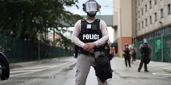 Miami-Dade police officers watch as demonstrators walk past during a protest against police brutality and the recent death of George Floyd on June 02, 2020.