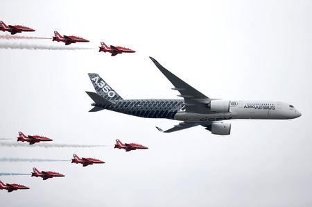 FILE PHOTO: An Airbus A350 aircraft flies in formation with Britain's Red Arrows flying display team at the Farnborough International Airshow in Farnborough