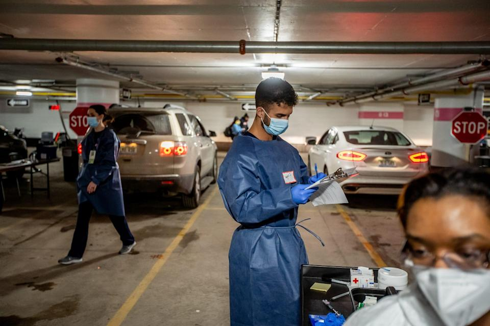Amjed Jadallah goes over paperwork while working to administer shots of the Moderna COVID-19 vaccine in an underground parking garage at TCF Center in downtown Detroit on Wednesday, February 3, 2021 as part of a drive-up distribution for the city of Detroit.