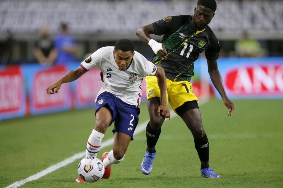 United States defender Reggie Cannon (2) gets past Jamaica forward Daryl Dike (11) with control of the ball in the second half of a CONCACAF Gold Cup quarterfinals soccer match, Sunday, July 25, 2021, in Arlington, Texas. (AP Photo/Brandon Wade)