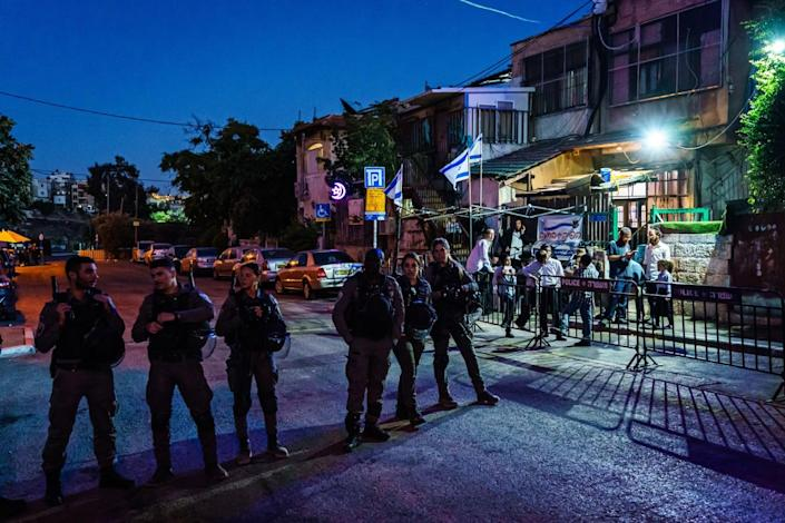 Israeli security officers form a loose line blocking a street