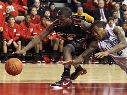 Rutgers' Eli Carter, left, dribbles as Seton Hall's Fuquan Edwin dives for the ball during the first half of an NCAA college basketball game in Piscataway, N.J., Wednesday, Feb. 8, 2012. (AP Photo/Mel Evans)