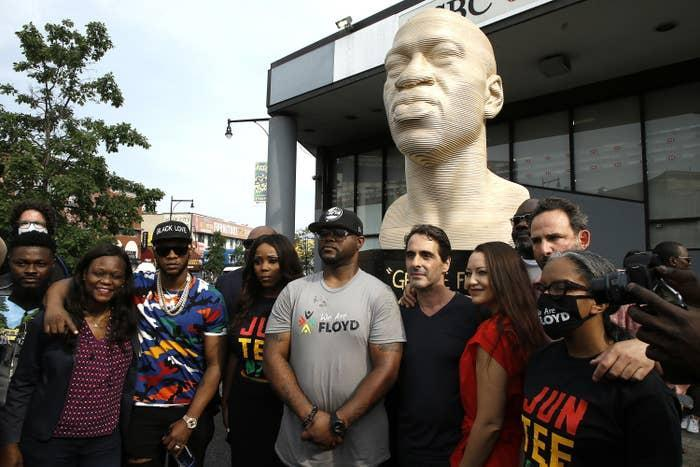Terrence Floyd (middle in a gray shirt) stands with others during the unveiling of a George Floyd statue in the Flatbush neighborhood of Brooklyn, New York.