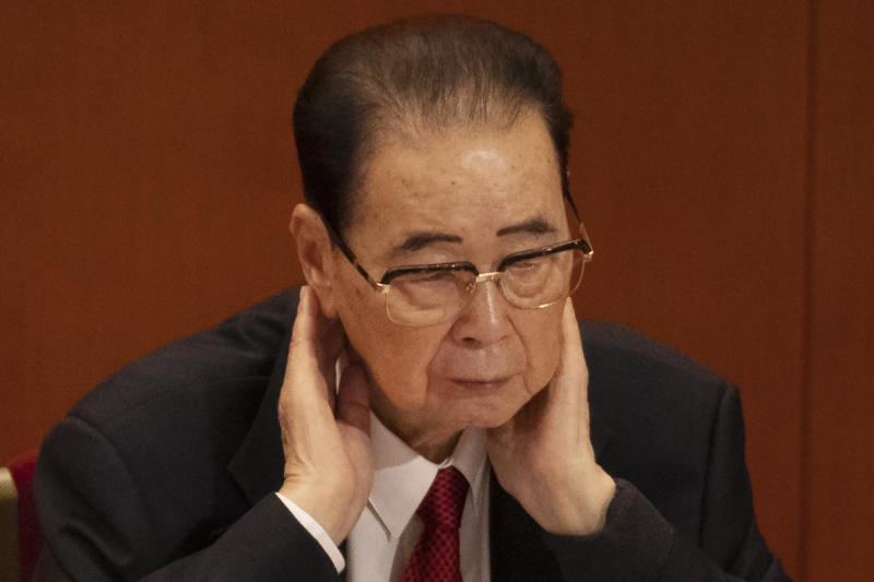 CORRECTS AGE TO 90, INSTEAD OF 91 - In this Oct. 24, 2017, photo, former Chinese Premier Li Peng, places his hands around his neck during the closing session of China's 19th Party Congress at the Great Hall of the People in Beijing, China. Li Peng, a former hard-line Chinese premier best known for announcing martial law during the 1989 Tiananmen Square pro-democracy protests, has died on Monday July 22, 2019 of unspecified illness. He was 90. (AP Photo/Ng Han Guan)
