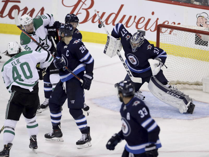 Winnipeg Jets goaltender Connor Hellebuyck (37) makes a blocker save against the Dallas Stars during the third period of an NHL hockey game Sunday, March 18, 2018, in Winnipeg, Manitoba. (Trevor Hagan/The Canadian Press via AP)