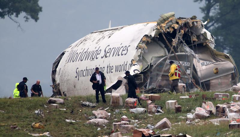 Investigators look through debris of a UPS A300 cargo plane after it crashed on approach at Birmingham-Shuttlesworth International Airport, Wednesday, Aug. 14, 2013, in Birmingham, Ala. The two pilots aboard the airplane were killed. (AP Photo/Hal Yeager)