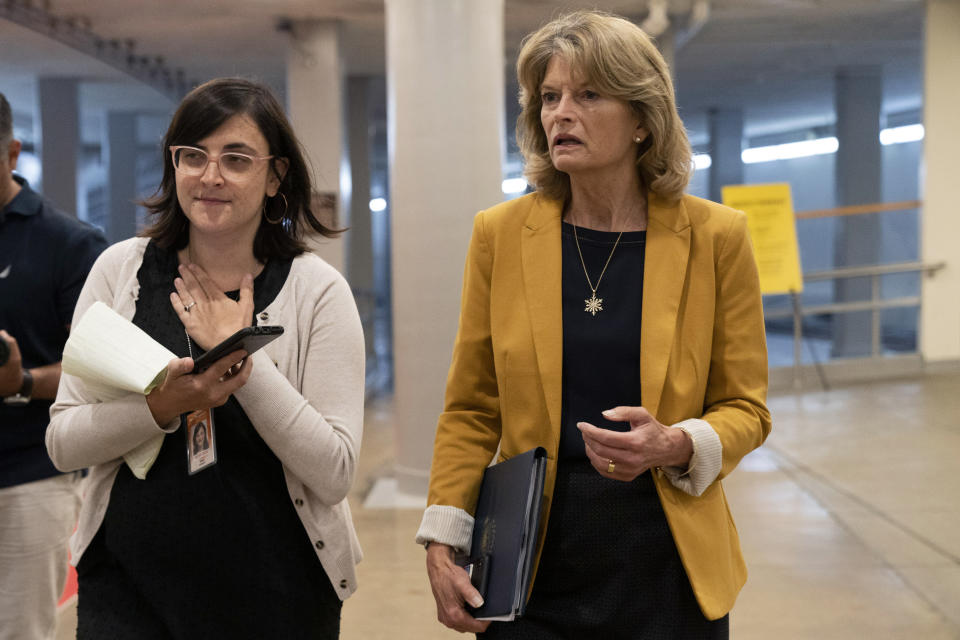 Sen. Lisa Murkowski, R-Alaska, right, speaks with a reporter while arriving for a Senate vote, Wednesday, June 16, 2021, on Capitol Hill in Washington. (AP Photo/Jacquelyn Martin)