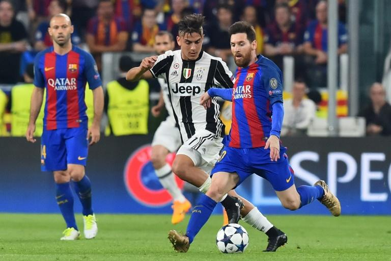Juventus' Paulo Dybala (C-L) fights for the ball with Barcelona's Lionel Messi during their UEFA Champions League quarter-final 1st leg match, at the Juventus stadium in Turin, on April 11, 2017