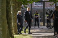 """King Willem-Alexander, second left, arrives to officially unveil a new monument in the heart of Amsterdam's historic Jewish Quarter on Sunday, Sept. 19, 2021, honoring the 102,000 Dutch victims of the Holocaust. Designed by Polish-Jewish architect Daniel Libeskind, the memorial is made up of walls shaped to form four Hebrew letters spelling out a word that translates as """"In Memory Of."""" The walls are built using bricks each of which is inscribed with the name of one of the 102,000 Jews, Roma and Sinti who were murdered in Nazi concentration camps during World War II or who died on their way to the camps. (AP Photo/Peter Dejong)"""