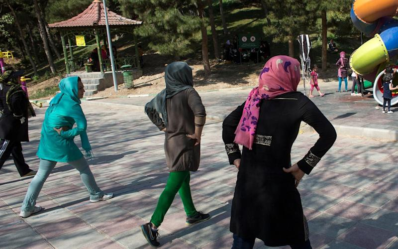 Women exercise in a park in Tehran. Two girls and four boys have been arrested for teaching dance moves including those from Zumba. - Alamy