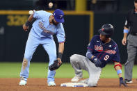Texas Rangers shortstop Isiah Kiner-Falefa, left, tries to tag Minnesota Twins Andrelton Simmons, right, who reached second on a double in the sixth inning at a baseball game Sunday, June 20, 2021, in Arlington, Texas. (AP Photo/Richard W. Rodriguez)