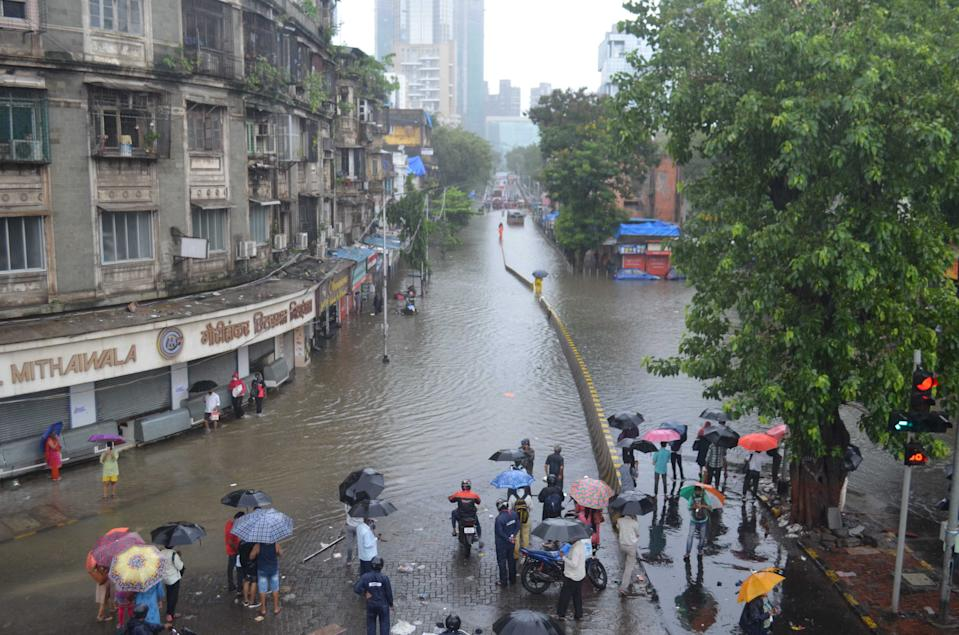 People waiting at a flooded road in Mumbai on August 4, 2020. (Photo by Arun Patil)