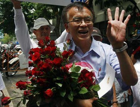 File photo: Somsak holds flowers and waves to his supporters before leaving police station in Bangkok