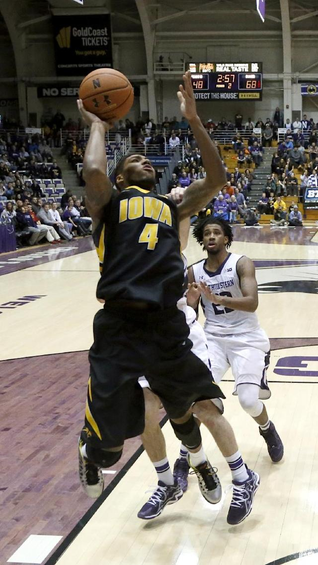 Iowa guard Roy Devyn Marble (4) is fouled from behind by Northwestern guard Dave Sobolewski as JerShon Cobb (23) watches during the second half of an NCAA college basketball game Saturday, Jan. 25, 2014, in Evanston, Ill. Iowa won 76-50. (AP Photo/Charles Rex Arbogast)