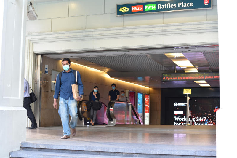 Subway commuters emerge from the Raffles Place MRT exit in Singapore Tuesday, June 2, 2020. Singapore reopened 75 percent of its economy Tuesday, as part of a three-phase controlled approach to end a virus lockdown since early April. (AP Photo/YK Chan)