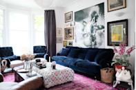 """<p>""""We've had this blue velvet sofa for years, it's really deep and comfortable but we are desperate to re-upholster it in something new - probably using stripes,"""" says Angus. """"The armchairs are antique, we reupholstered them using ticking stripes and dark blue velvet. We made our ottoman out of a rug we designed, and the huge pink rug is vintage. Our latest gift to ourselves is an antique stone swan planter, which you can just see peeping into the left of the frame. Believe it or not the Foxgloves aren't real, you can get such amazing fake flowers these days - we're very into them. They are sitting in an original red fire bucket from the 1930s and we made the side table out of a vintage toboggan.""""</p>"""