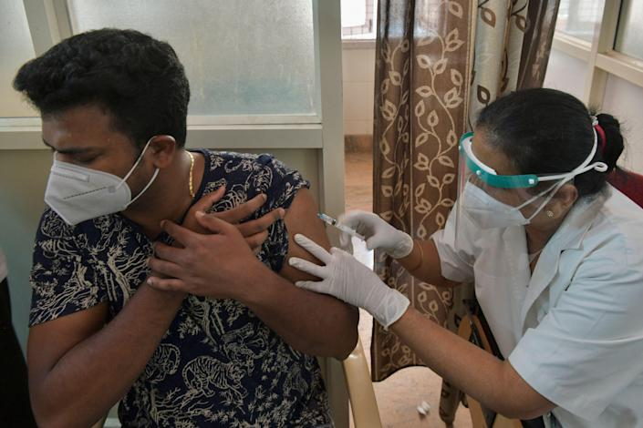 <p>A medical worker inoculates a man with a dose of Covid-19 vaccine at a vaccination centre in Bangalore on 7 May, 2021.</p> (AFP via Getty Images)