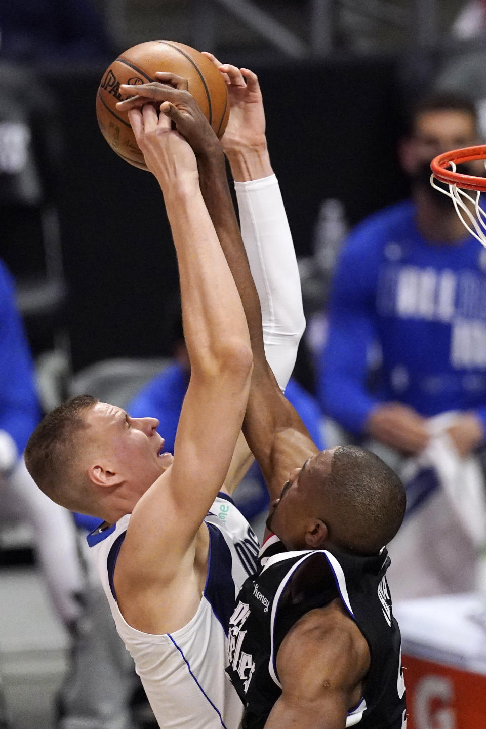 Dallas Mavericks center Kristaps Porzingis, left, shoots as Los Angeles Clippers center Serge Ibaka defends during the first half in Game 1 of an NBA basketball first-round playoff series Saturday, May 22, 2021, in Los Angeles. (AP Photo/Mark J. Terrill)